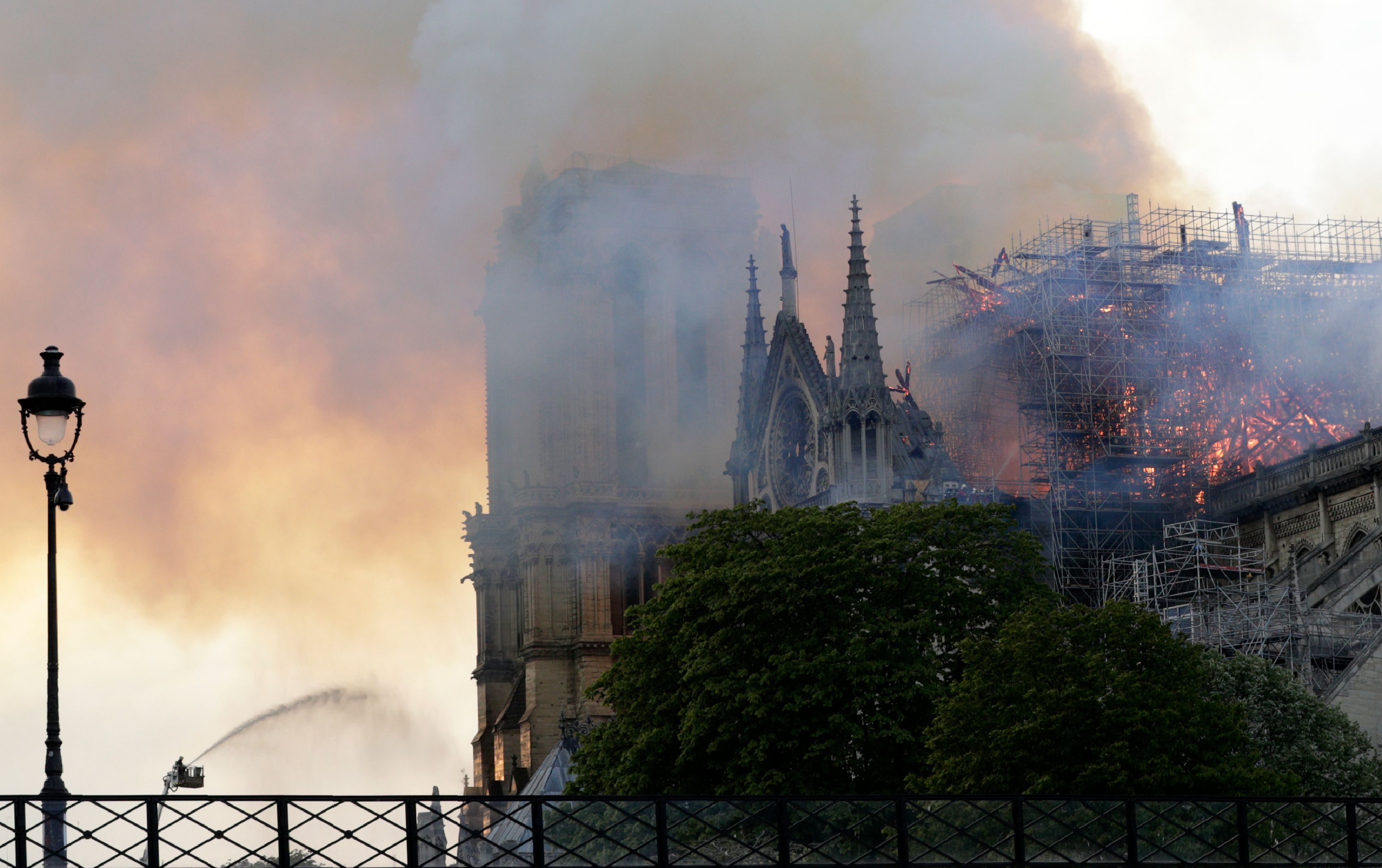A firefighter uses a hose to douse flames and smoke billowing from the roof at Notre-Dame Cathedral in Paris on April 15, 2019. - A fire broke out at the landmark Notre-Dame Cathedral in central Paris, potentially involving renovation works being carried out at the site, the fire service said.Images posted on social media showed flames and huge clouds of smoke billowing above the roof of the gothic cathedral, the most visited historic monument in Europe. (Photo by Geoffroy VAN DER HASSELT / AFP)        (Photo credit should read GEOFFROY VAN DER HASSELT/AFP/Getty Images)