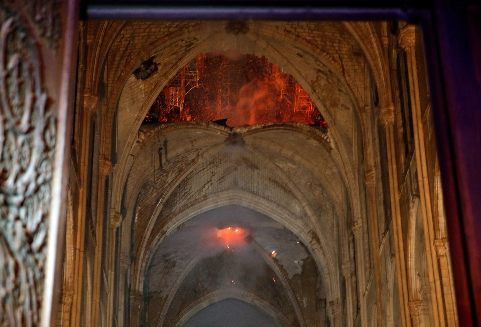 Flames and smoke are seen as the interior of the Notre-Dame Cathedral continues to burn on April 15, 2019, in the French capital Paris. - A huge fire swept through the roof of the famed Notre-Dame Cathedral in central Paris on April 15, 2019, sending flames and huge clouds of grey smoke billowing into the sky. The flames and smoke plumed from the spire and roof of the gothic cathedral, visited by millions of people a year. A spokesman for the cathedral told AFP that the wooden structure supporting the roof was being gutted by the blaze. (Photo by PHILIPPE WOJAZER / POOL / AFP)        (Photo credit should read PHILIPPE WOJAZER/AFP/Getty Images)