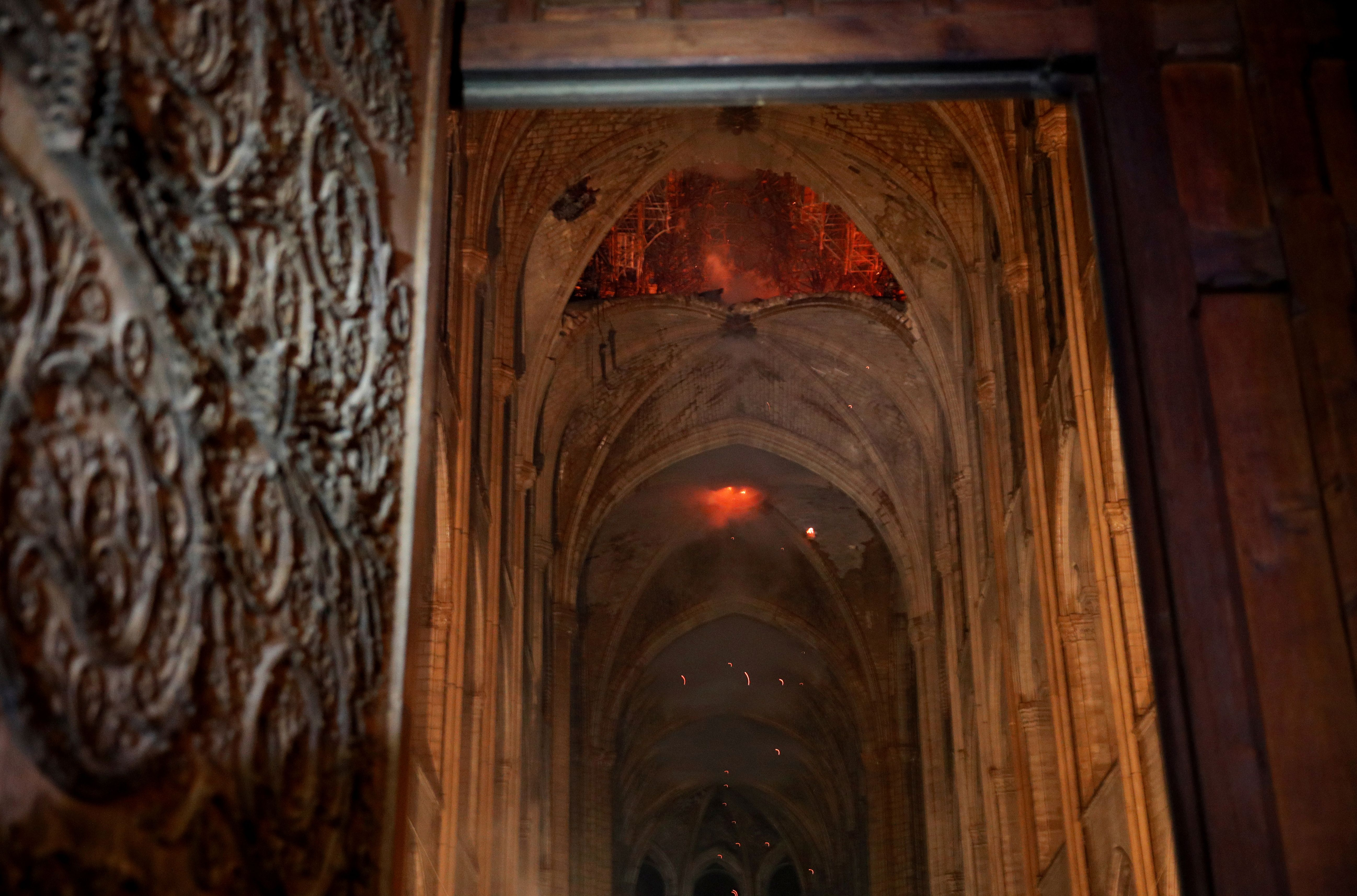 Flames and smoke rise from the interior of Notre-Dame Cathedral in Paris on April 15, 2019, after a fire engulfed the building. - A huge fire swept through the roof of the famed Notre-Dame Cathedral in central Paris on April 15, 2019, sending flames and huge clouds of grey smoke billowing into the sky. The flames and smoke plumed from the spire and roof of the gothic cathedral, visited by millions of people a year. A spokesman for the cathedral told AFP that the wooden structure supporting the roof was being gutted by the blaze. (Photo by PHILIPPE WOJAZER / POOL / AFP)        (Photo credit should read PHILIPPE WOJAZER/AFP/Getty Images)