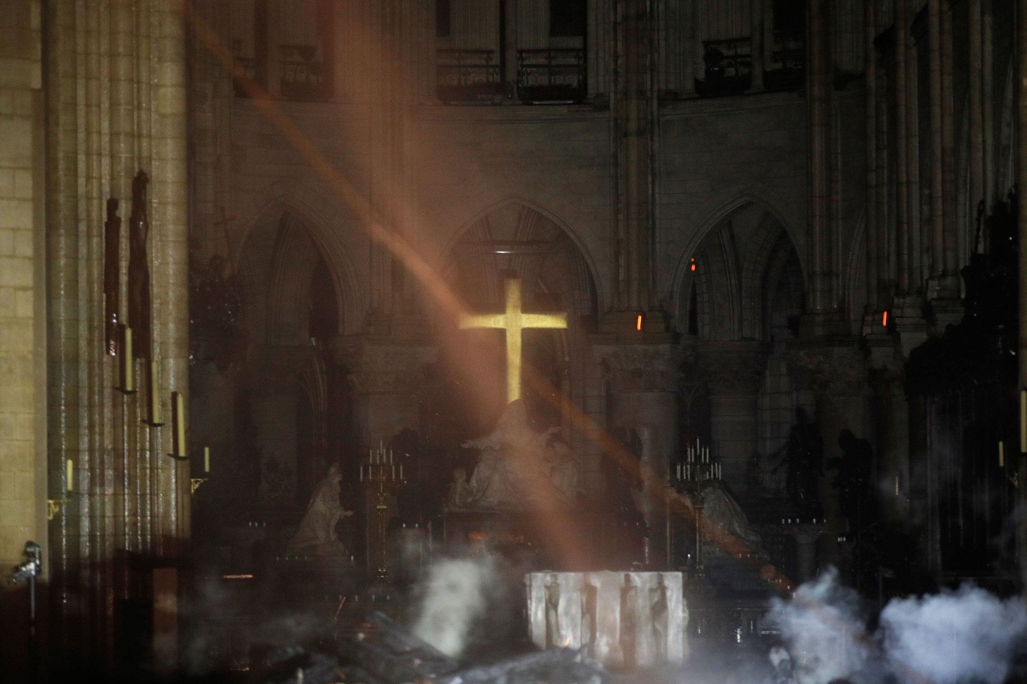 Smoke rises around the alter in front of the cross inside the Notre-Dame Cathedral as the fire continues to burn on April 16, 2019 in the French capital Paris. - A huge fire swept through the roof of the famed Notre-Dame Cathedral in central Paris on April 15, 2019, sending flames and huge clouds of grey smoke billowing into the sky. The flames and smoke plumed from the spire and roof of the gothic cathedral, visited by millions of people a year. A spokesman for the cathedral told AFP that the wooden structure supporting the roof was being gutted by the blaze. (Photo by PHILIPPE WOJAZER / POOL / AFP)        (Photo credit should read PHILIPPE WOJAZER/AFP/Getty Images)