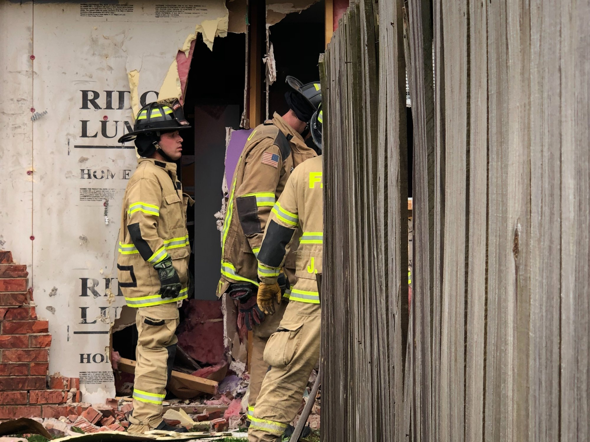 Firefighters pull a white Chevrolet Tahoe from the side of a home on High Avenue in Fayetteville on Thursday, May 30, 2019, after the Tahoe hit the house. (KFSM)
