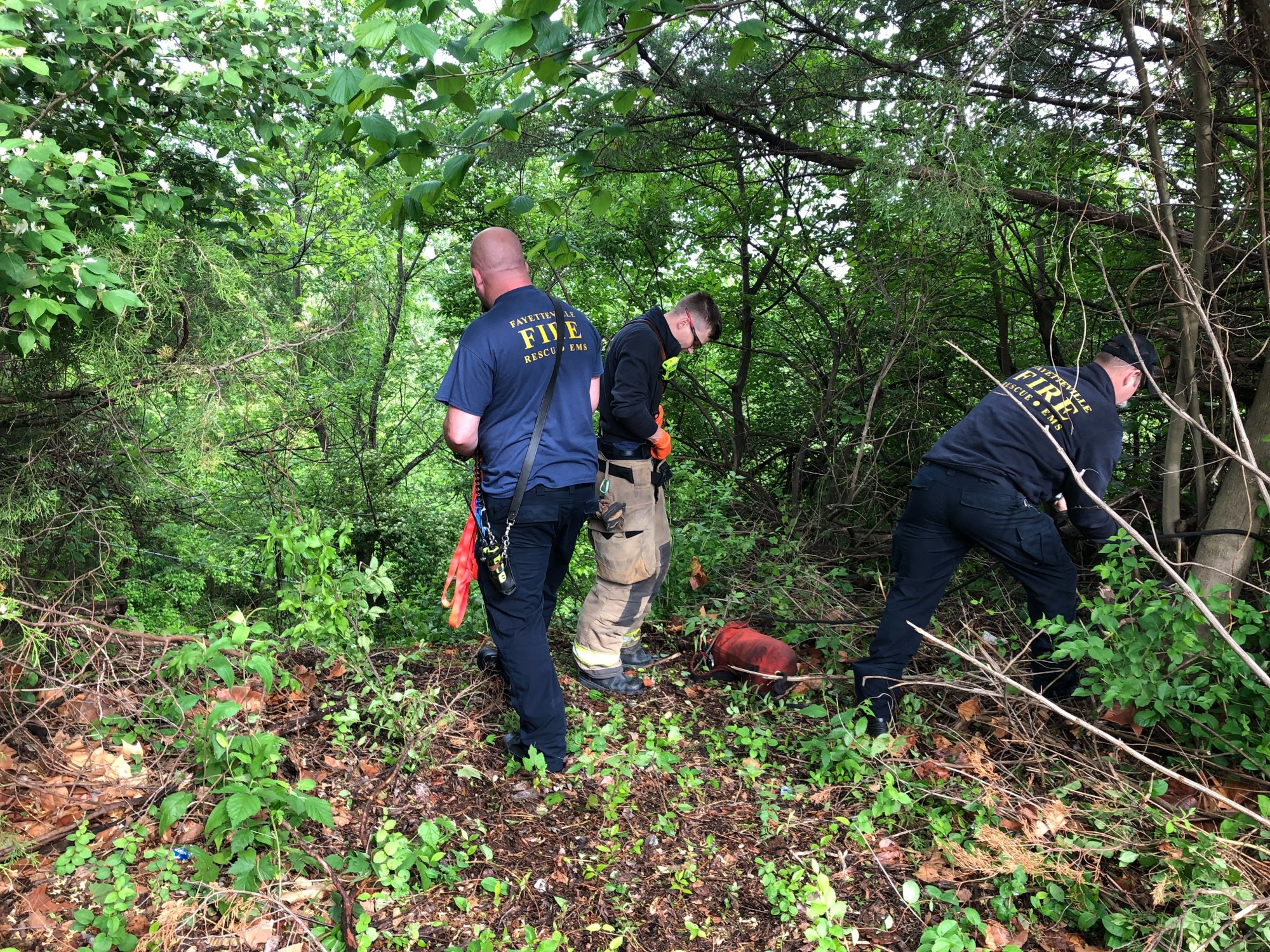 Rescue personnel gear up to reach an SUV that drove off a cliff behind the Northwest Arkansas Mall in Fayetteville on May 2, 2019. (KFSM)
