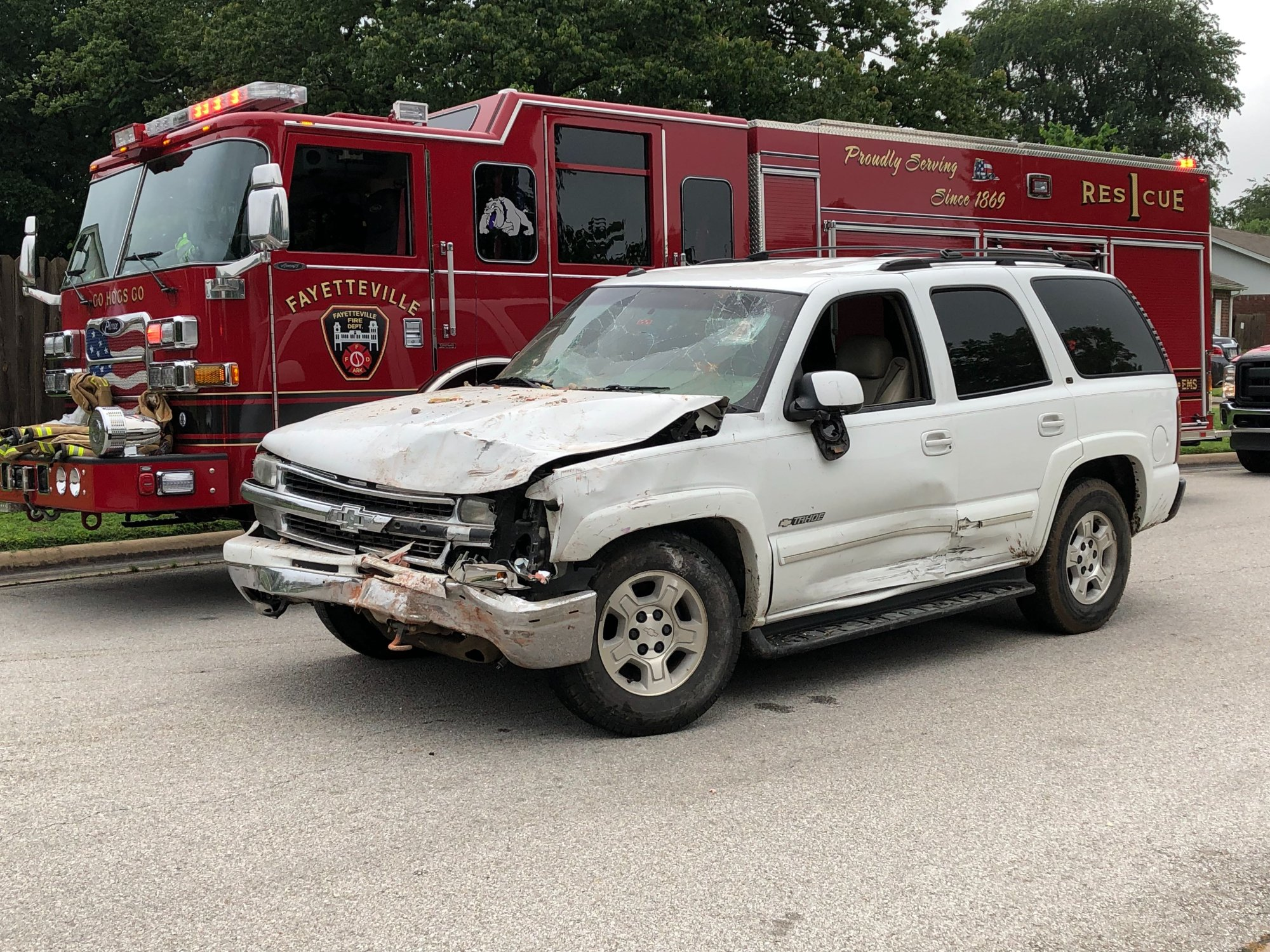 A white Chevrolet Tahoe shows front-end damage where it hit a brick house on High Avenue in Fayetteville on Thursday, May 30, 2019. (KFSM)