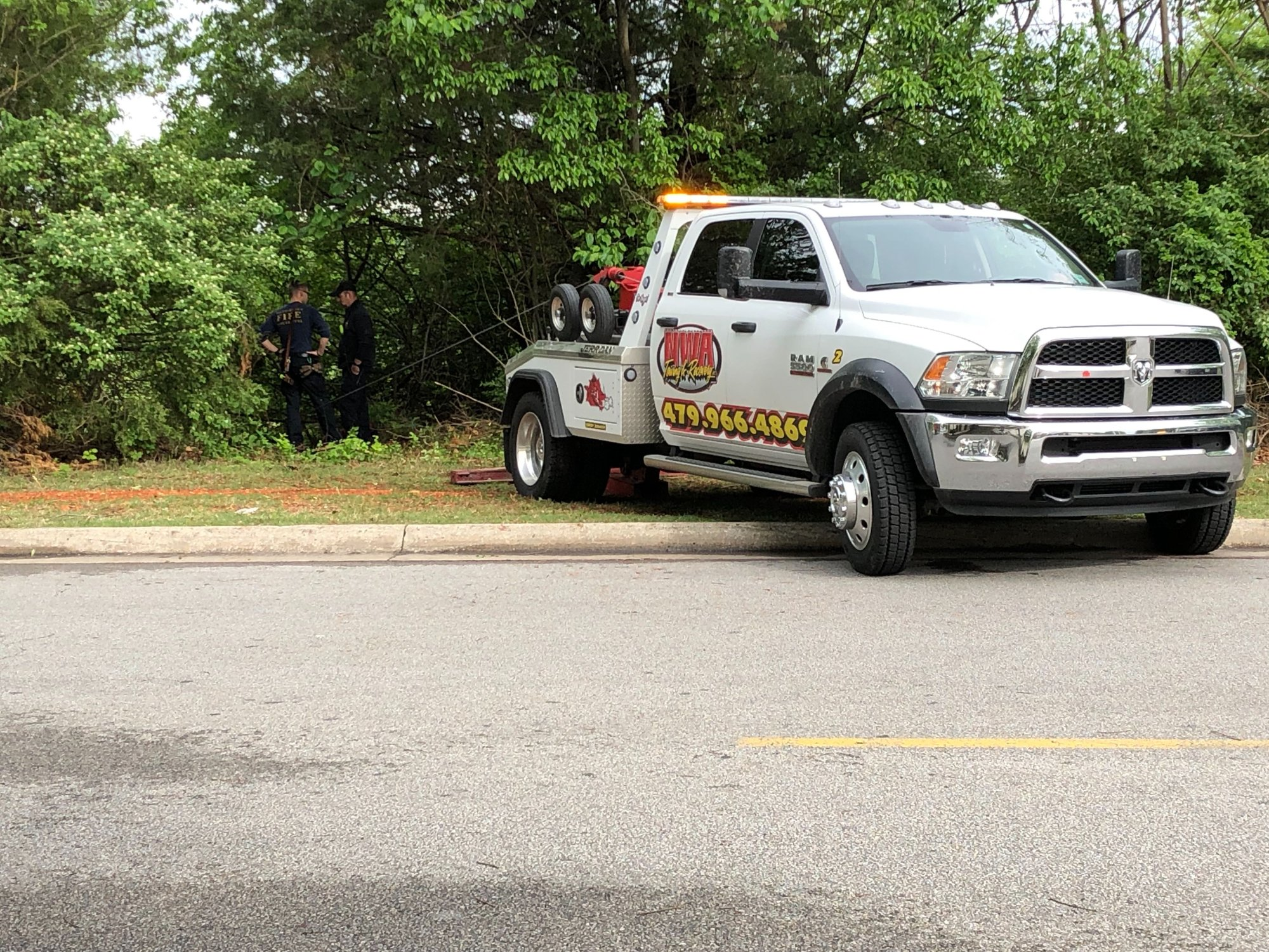 A tow truck attempts to pull an SUV up a cliff behind the Northwest Arkansas Mall after an accident Thursday, May 2, 2019. (KFSM)