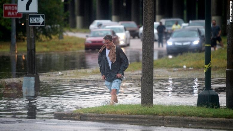 A man walks through standing water in New Orleans.