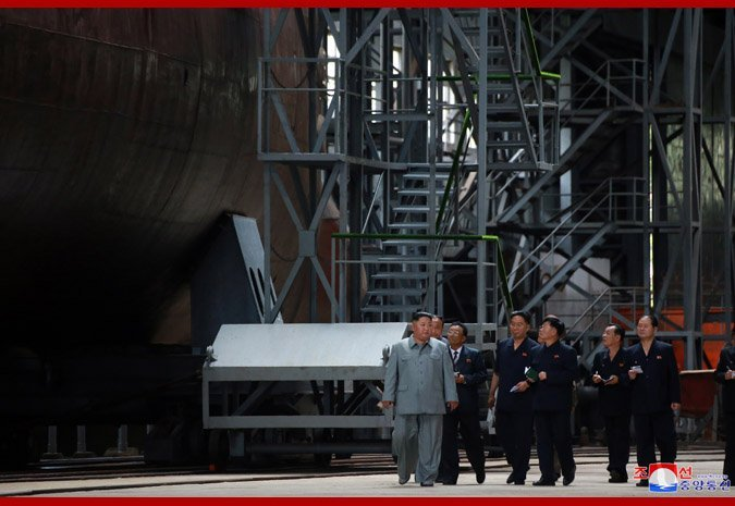 North Korean leader Kim Jong Un is seen standing beside a submarine under construction in this photograph released by North Korean state media.