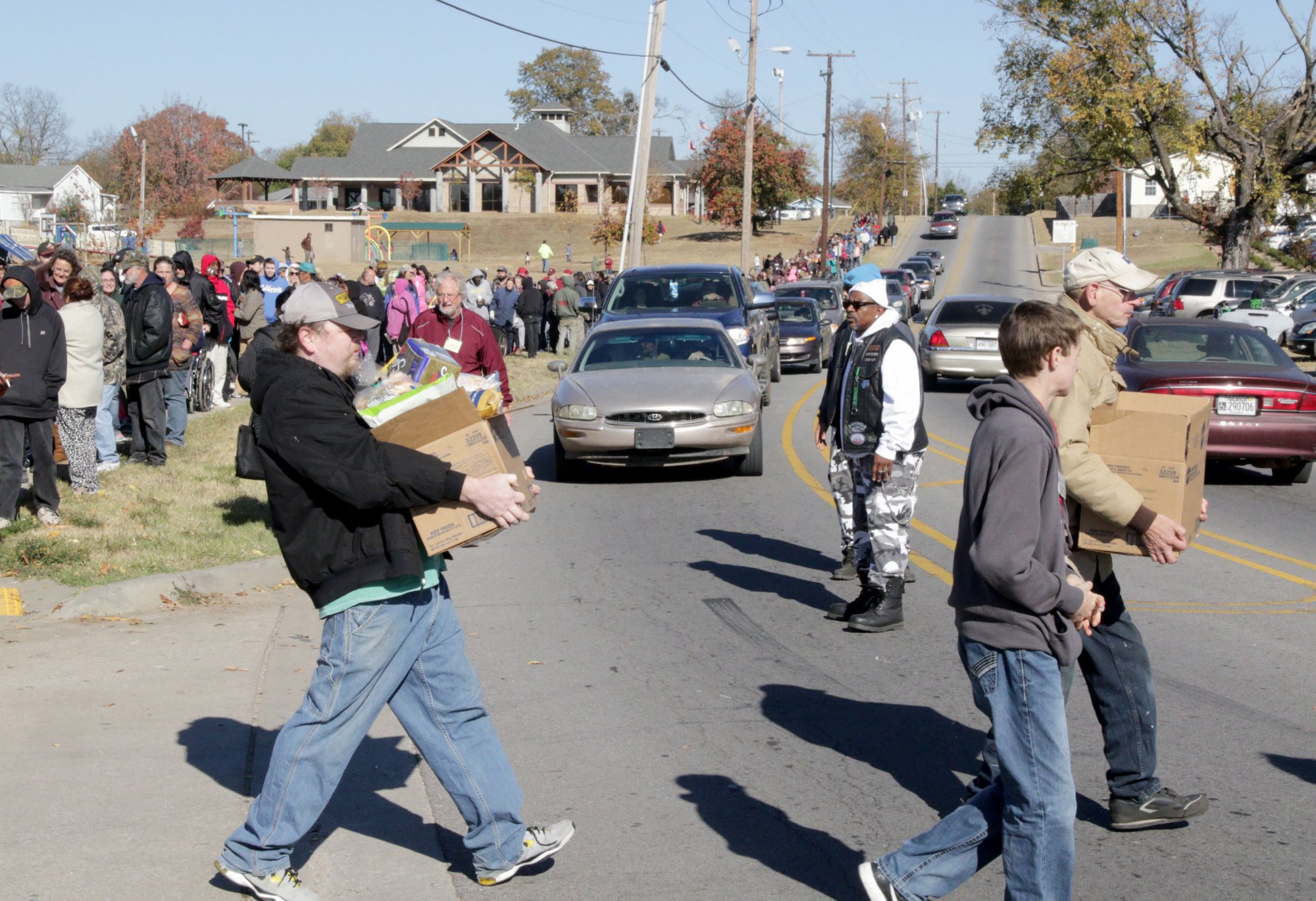 Members of the Ruff Ryders Motorcycle Club hold traffic to let pedestrians with food boxes cross Greenwood Ave.,  Saturday, Nov 19, 2016, at the quarterly Antioch in the Park food giveaway in Martin Luther King Jr. Park. JAMIE MITCHELL/TIMES RECORD